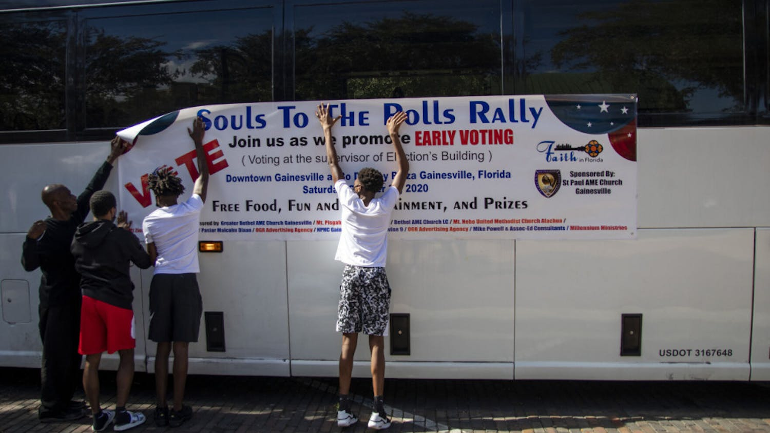 """Volunteers put up a """"Souls to The Polls"""" banner on a bus that takes people from Bo Diddley Plaza to the Alachua County Supervisor of Elections office on Saturday, Oct. 31, 2020."""