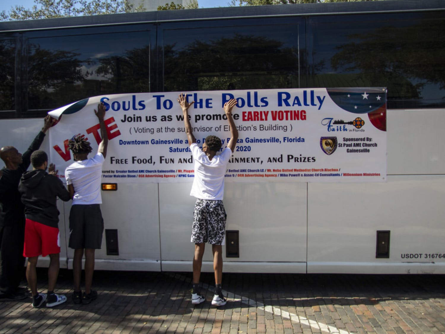 "Volunteers put up a ""Souls to The Polls"" banner on a bus that takes people from Bo Diddley Plaza to the Alachua County Supervisor of Elections office on Saturday, Oct. 31, 2020."
