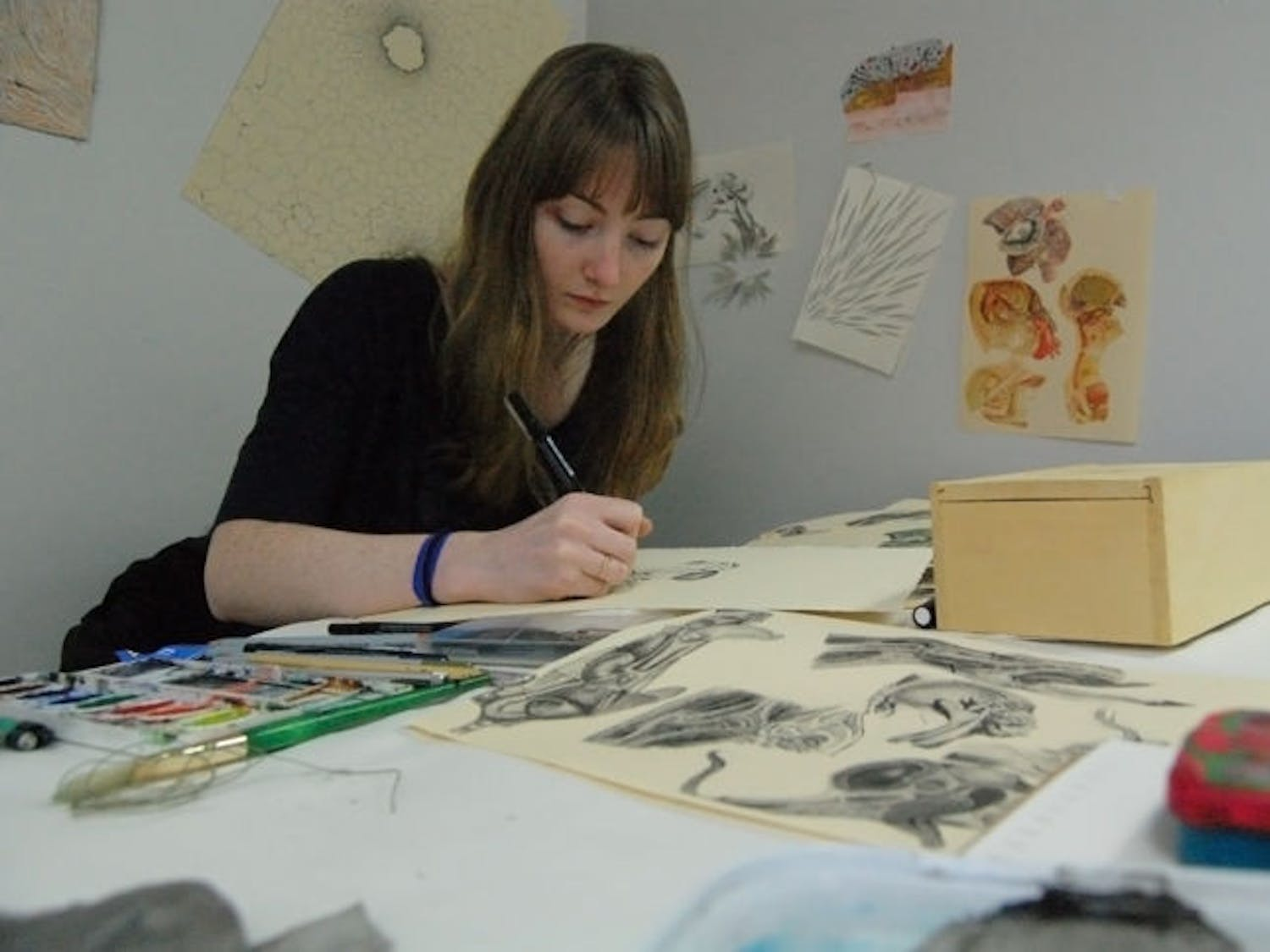 """Lily King, a 21-year-old UF drawing senior, draws anatomical figures she saw in various medical textbooks. She uses a micron pen to illustrate her mad scientist collages, and her work """"Contained"""" will be featured in Friday's exhibition."""