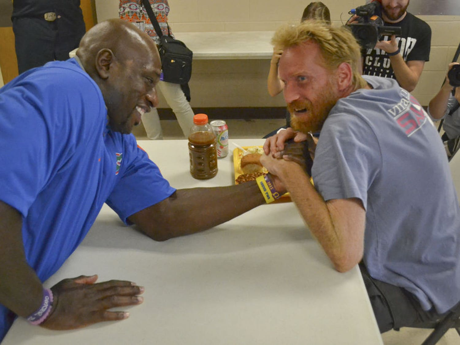 """Thaddeus Bullard (left), also known as WWE wrestler Titus O'Neil, arm wrestles Mike Grace, a 38-year-old homeless veteran, at St. Francis House on Oct. 2, 2015. Grace challenged Bullard to the match and won. """"I imagine he could pick me up and throw me across the room,"""" Grace said about Bullard."""