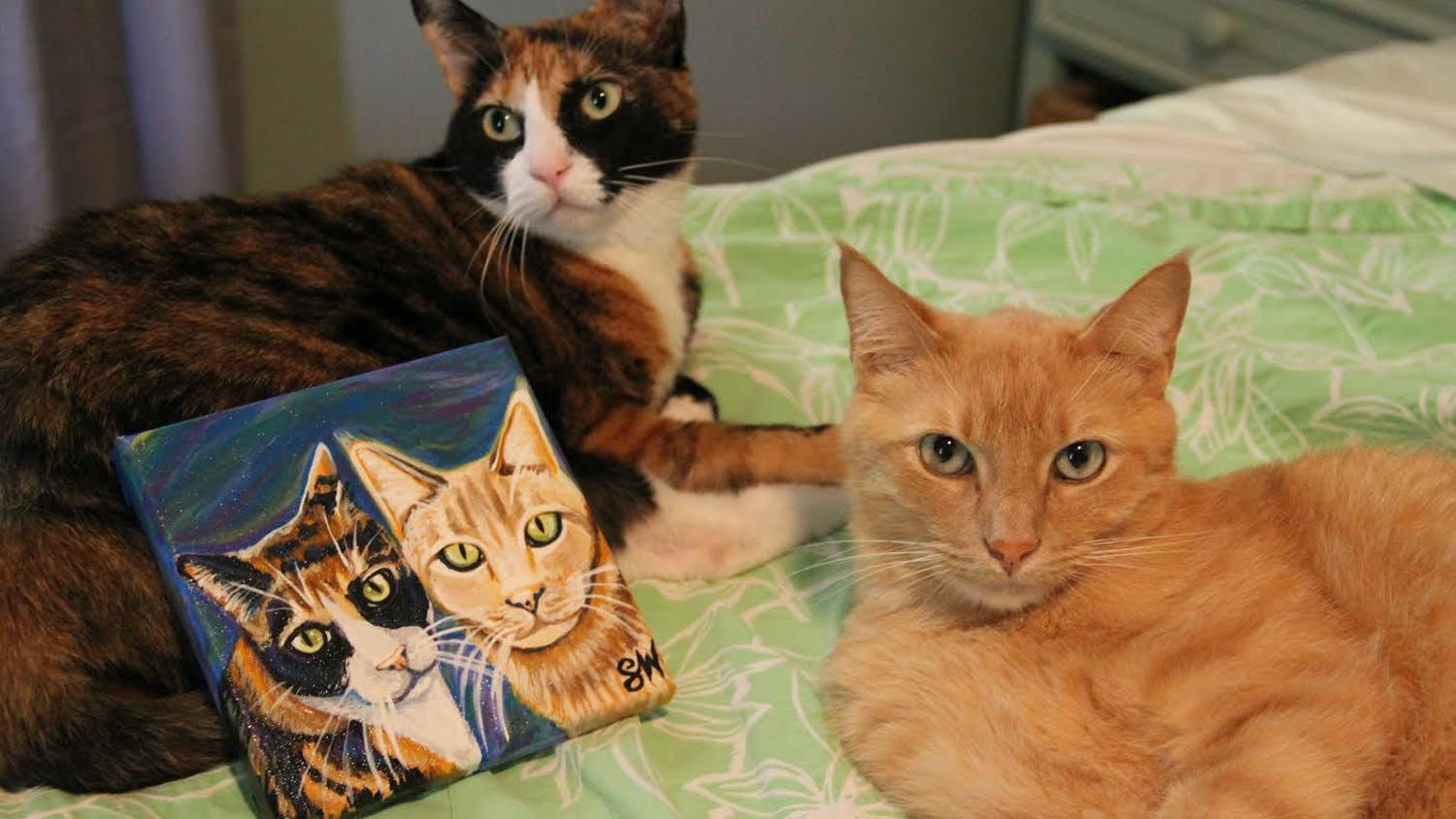Oka and Mango posing with their commissioned Samm Wehman Art Pet Portrait. (Courtesy by Samm Epstein)