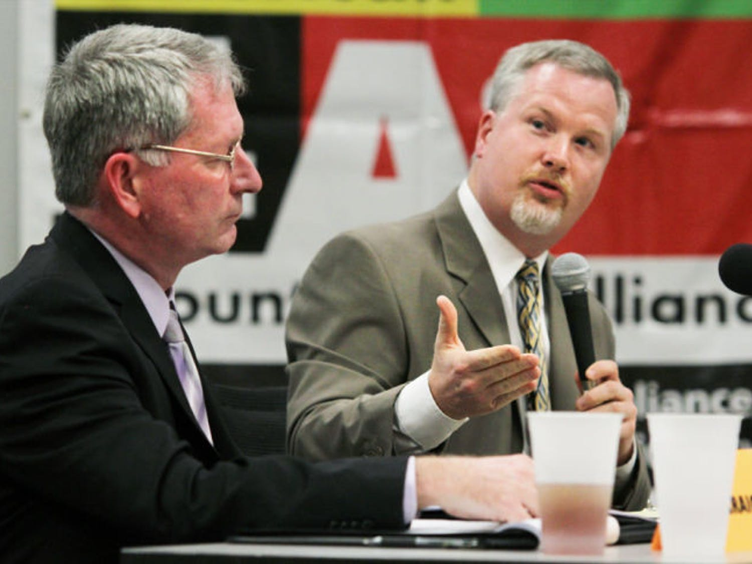 Gainesville mayor Craig Lowe listens to opponent Ed Braddy's rebuttal during a candidate forum at the Alachua County Health Department on Monday night. Read the story on page 4.