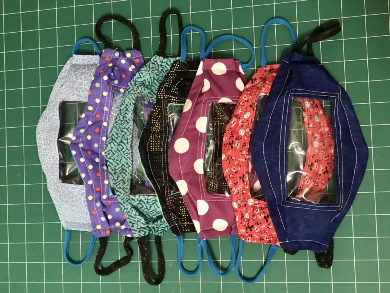 The masks are made from cotton quilting fabric, clear vinyl and T-shirt yarn.