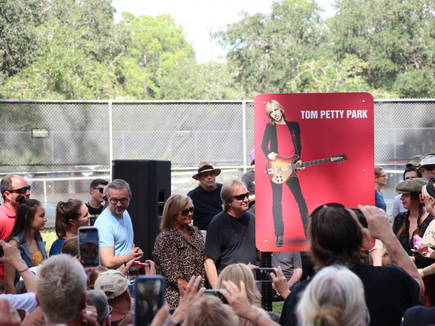 Tom Petty's family members and fans surround the newly installed sign in Tom Petty Park at the dedication ceremony held Oct. 20, 2018. Bruce and Adria Petty, brother and daughter to Tom, made short remarks before the unveiling.