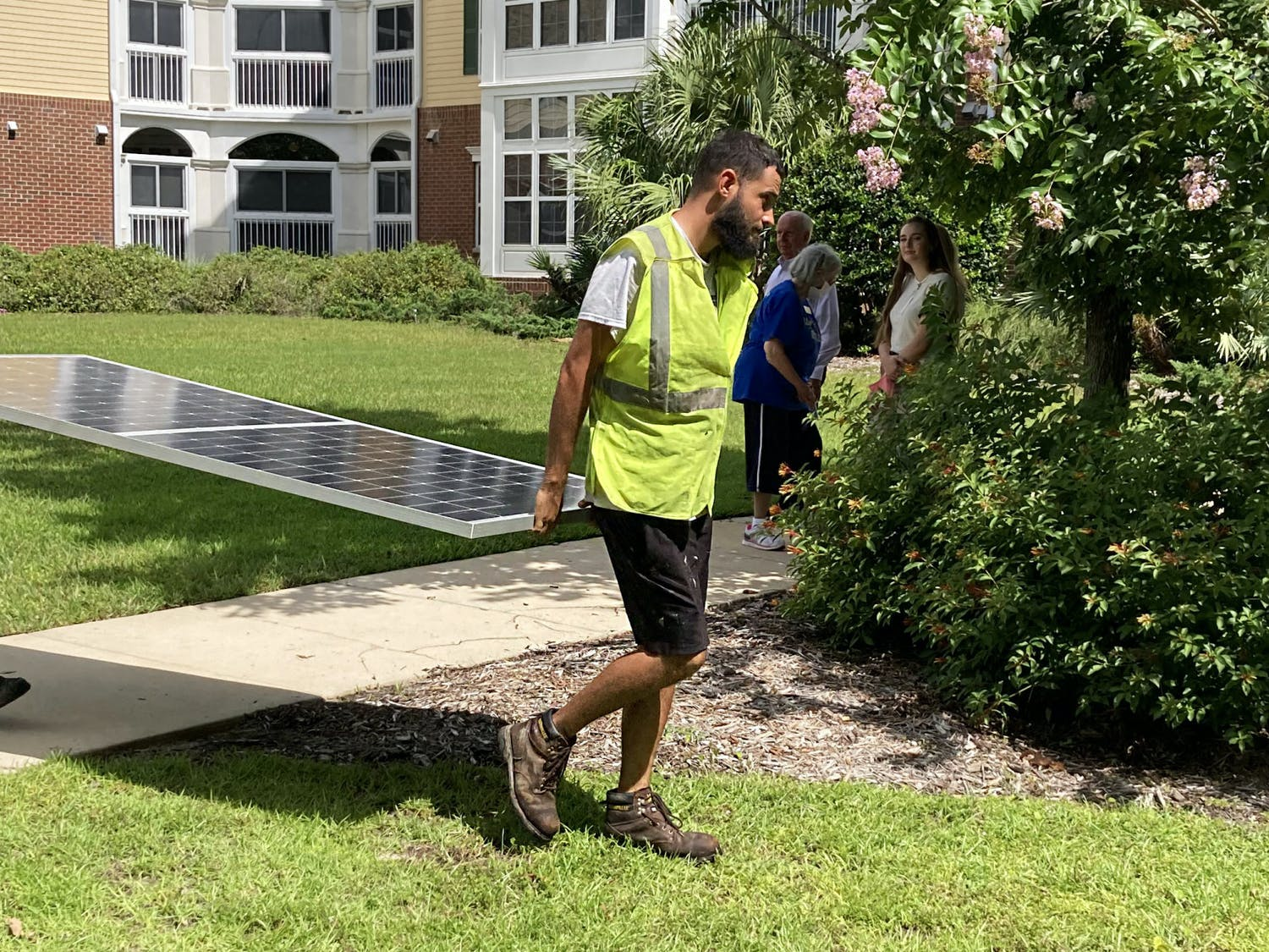 Workers lift up the first solar panel installed on the rooftops of Oak Hammock at the University of Florida on Tuesday, July 20, 2021.