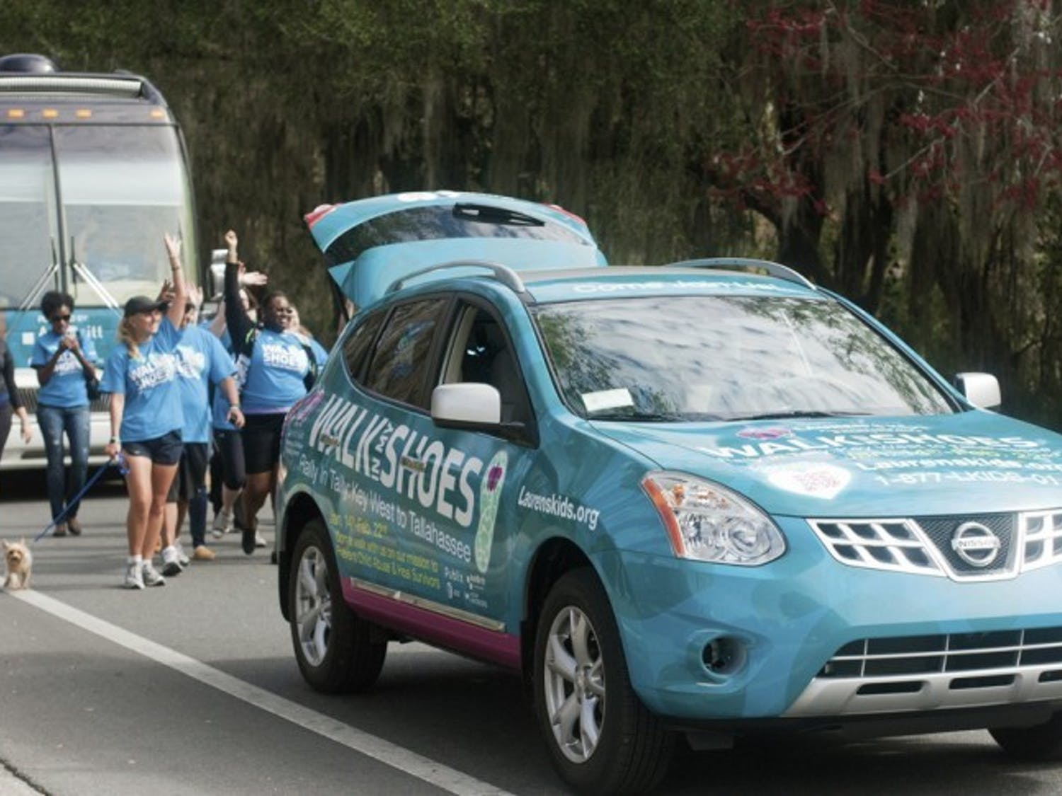"""Lauren Book, founder of Lauren's Kids, and her supporters wave at passing motorists at they walk down Museum Drive near Lake Alice on Tuesday as part of the """"Walk in My Shoes"""" campaign, which is a 1,500 mile walk across Florida to bring awareness to help prevent sexual abuse."""