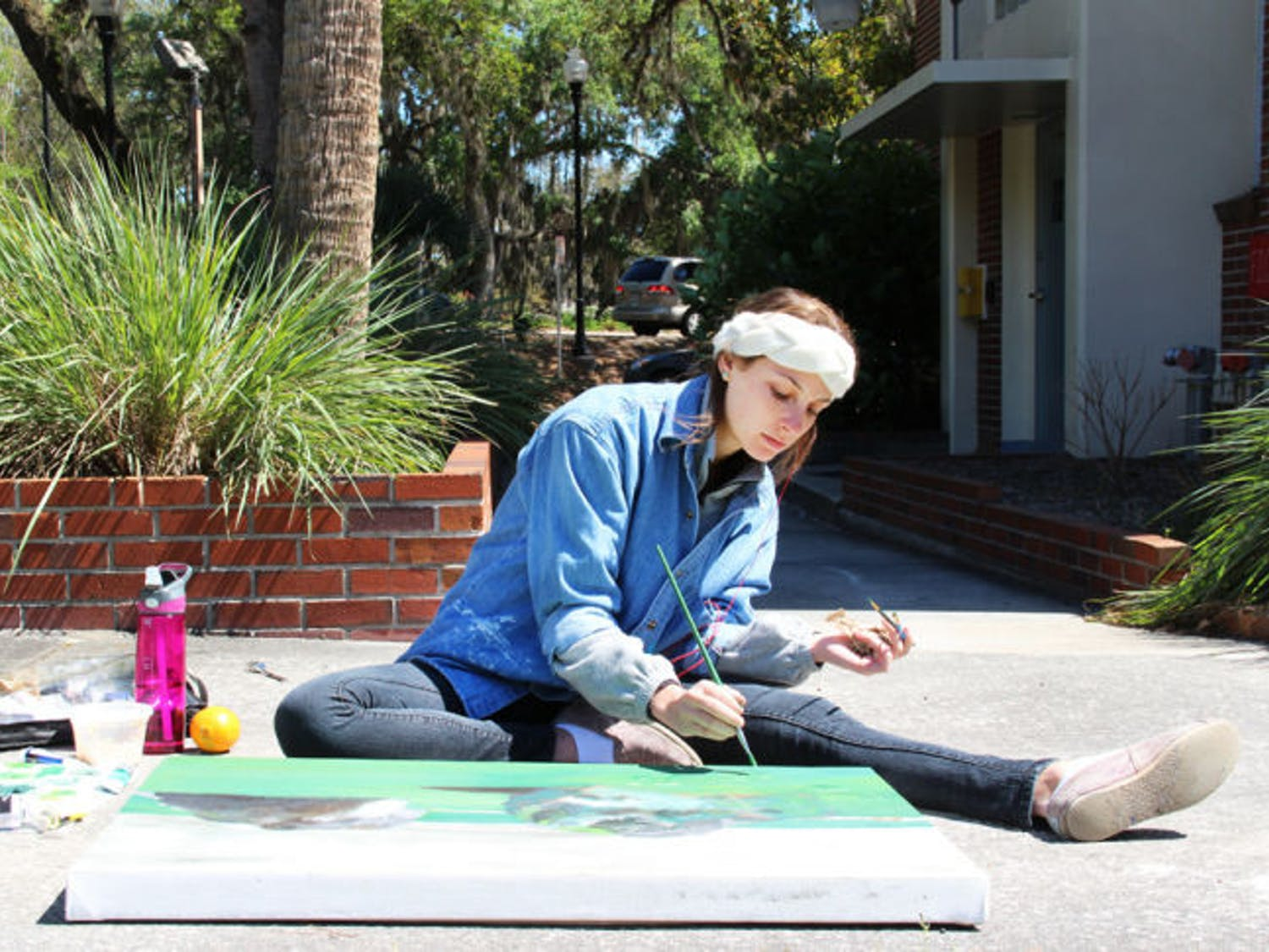 Dayna Lazarowitz, a 20-year-old UF graphic design student, paints a picture of two boulders outside Reid Hall Tuesday afternoon. Lazarowitz was given an assignment to paint outdoors for her art class.