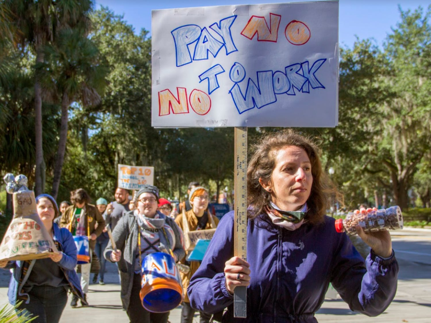 Shaking a bottle of peanuts, Paula Fernandez, a 31-year-old UF teaching assistant, protests fees for employees of the university