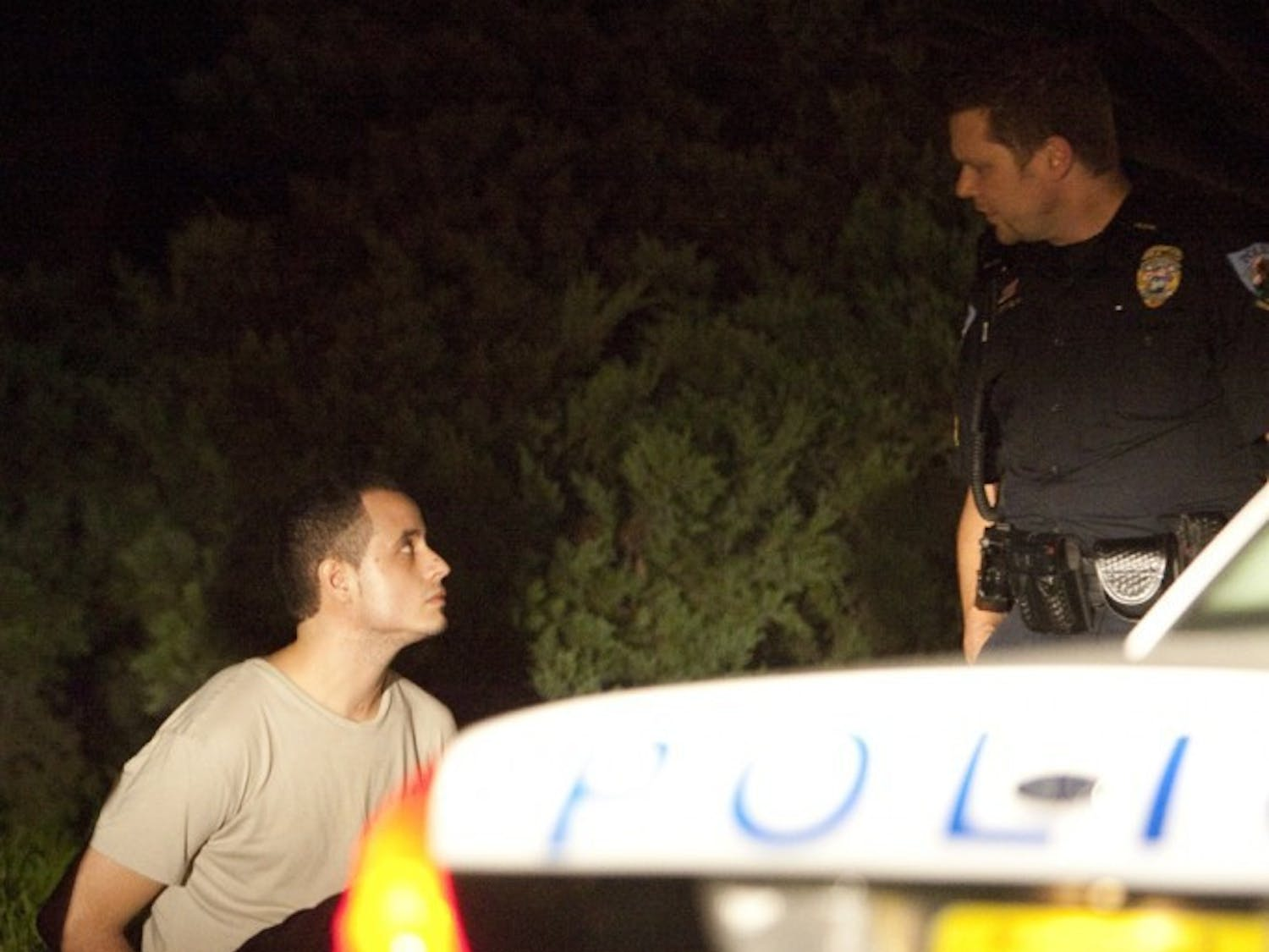 Police speak to the driver of a white Lexus sedan carrying suspects in a Thursday morning stabbing on UF's campus.