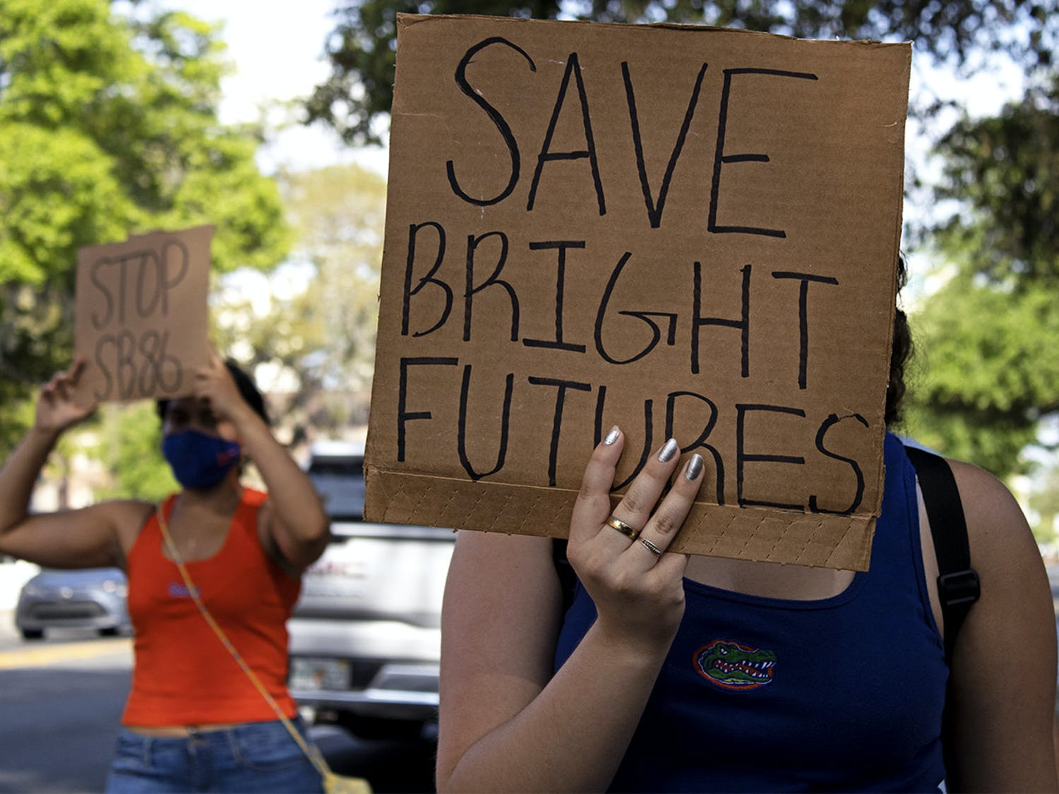 """Aleidys Lopez, 19, a UF sustainability studies and women's studies sophomore shields her face from the sun with a """"Save Bright Futures"""" sign as she three other protestors march down University Avenue on Friday, March 26, 2021. The protest was held to raise awareness about Senate Bill 86, which was amended on Tuesday."""