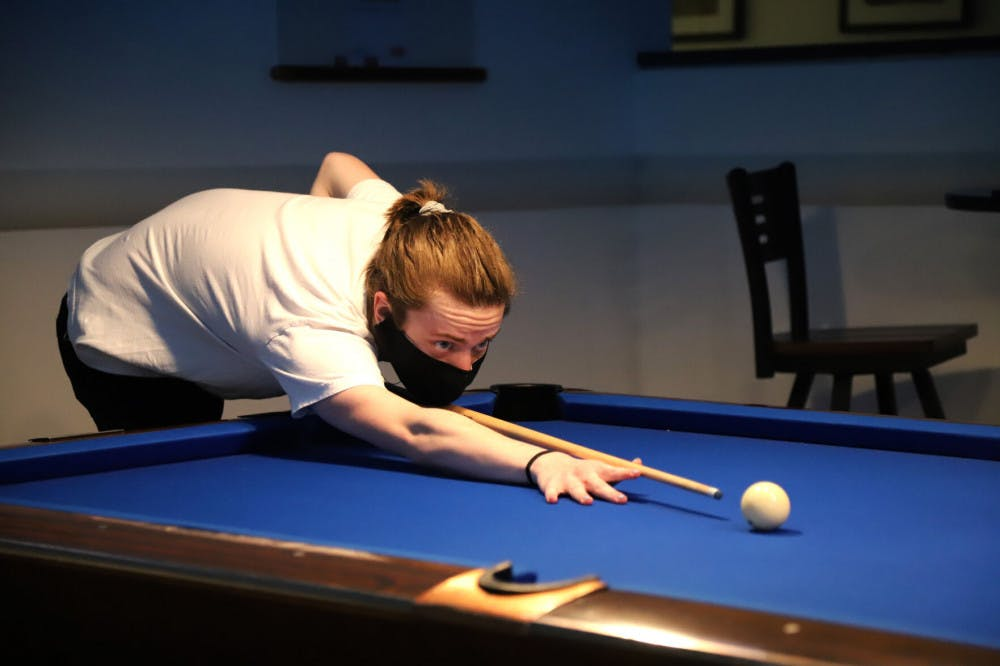 A picture of a person playing pool