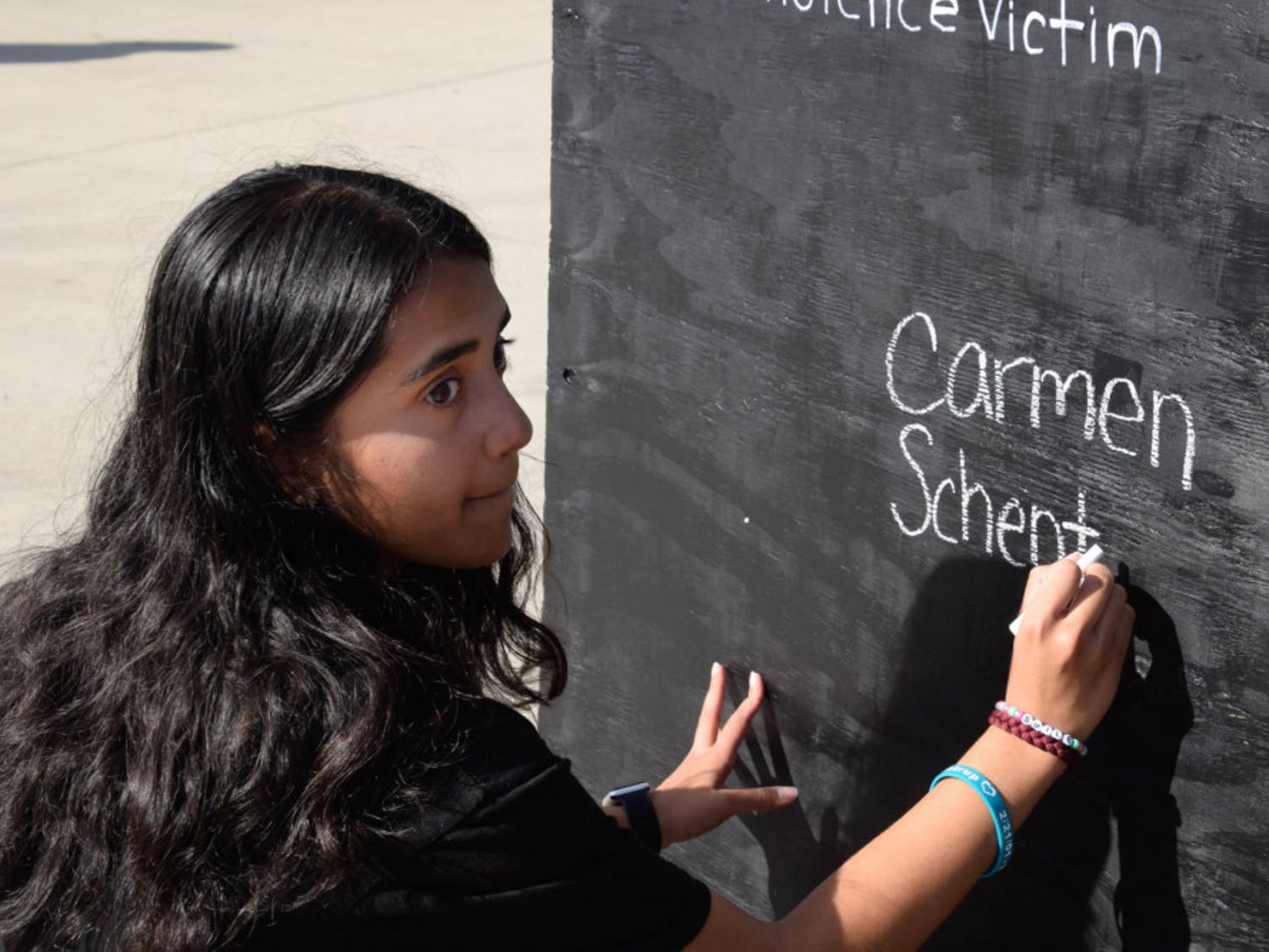 MSD alum Anisha Saripalli, an 18-year-old biomedical engineering sophomore and the March for Our Lives Gainesville treasurer, writes the name of her friend down on the gun violence victim board. Carmen Schentrup was a Marjory Stoneman Douglas student who died in the shooting just days after she was accepted into UF.