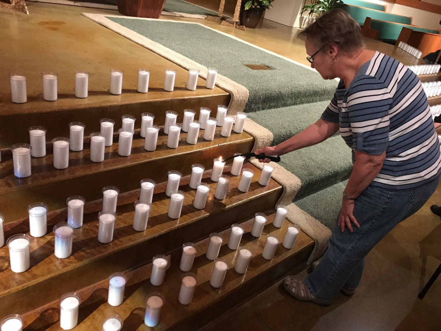 Susan Johnson bends to light one of the 352 candles in St. Patrick Catholic Church, located at 500 NE 16th Ave., on Thursday night. The candles, which represented the 352 inmates on death row in Florida, were part of the church's Cities for Life Day event.