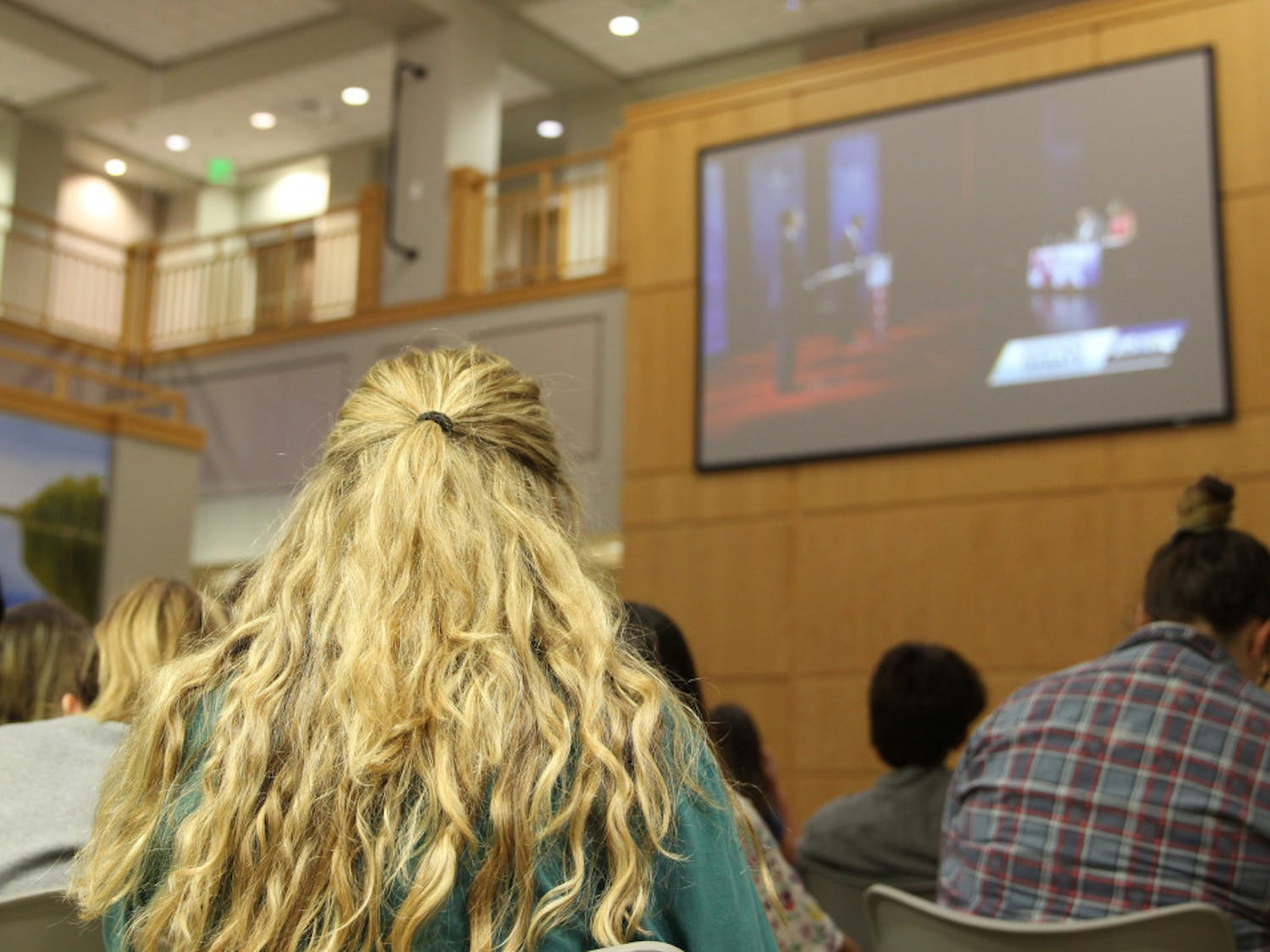 Grace Banahan, an18-year-old political science and journalism major, listens to Florida Governor candidates Ron DeSantis and Andrew Gillum debate on corruption and racism Wednesday night at the Governor's Debate Watch Party in Pugh Hall. Banahan is voting for her first time this year.