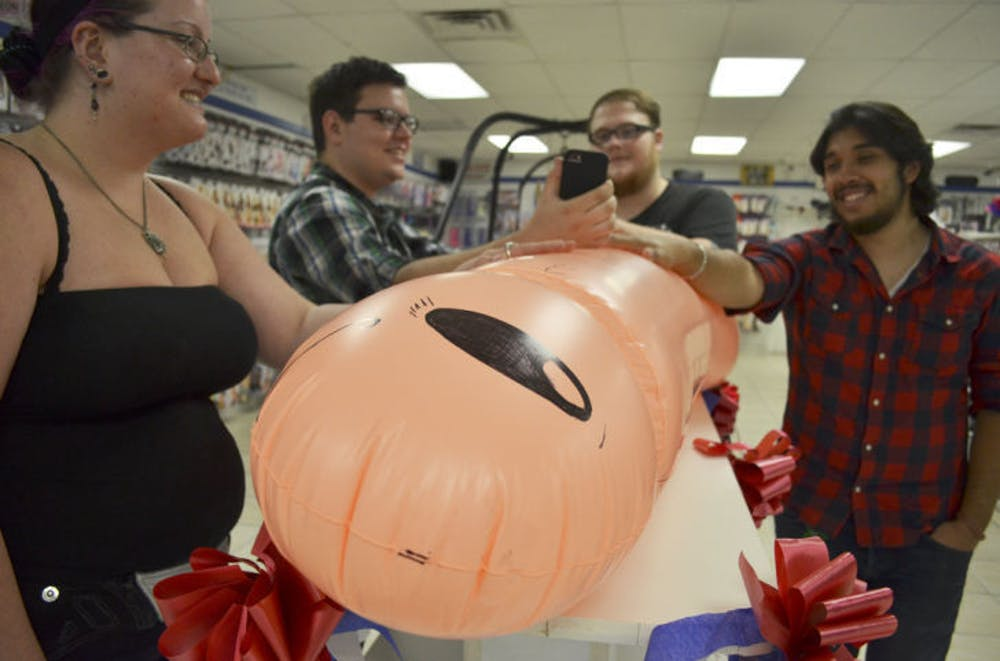 """<p>Contestants gather around a five-and-a-half foot long inflated penis for X-Mart's """"Longest Handy Ever Contest"""" held Saturday at the store.&nbsp;</p> <div>&nbsp;</div>"""
