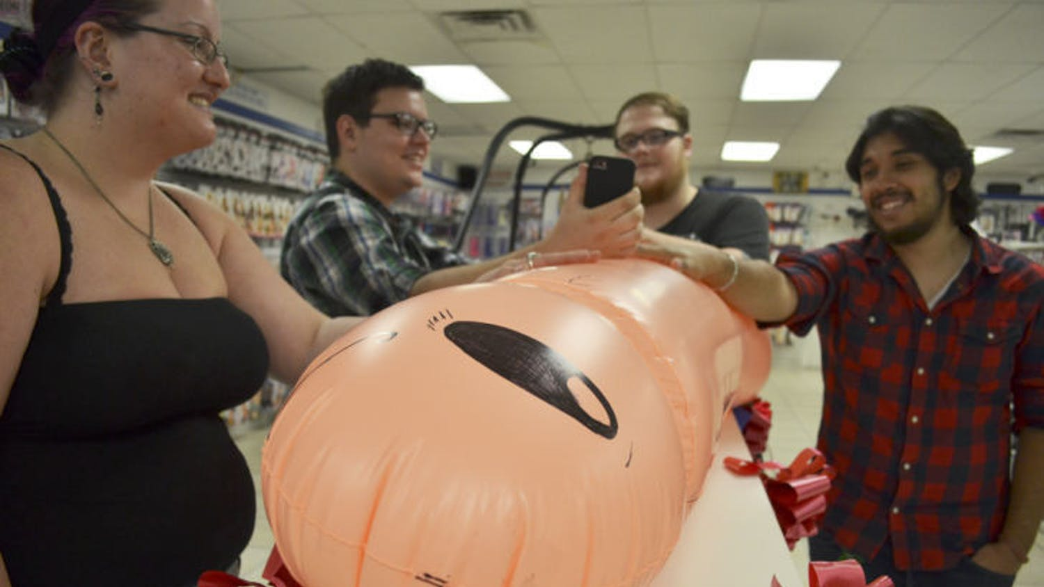 """Contestants gather around a five-and-a-half foot long inflated penis for X-Mart's """"Longest Handy Ever Contest"""" held Saturday at the store."""