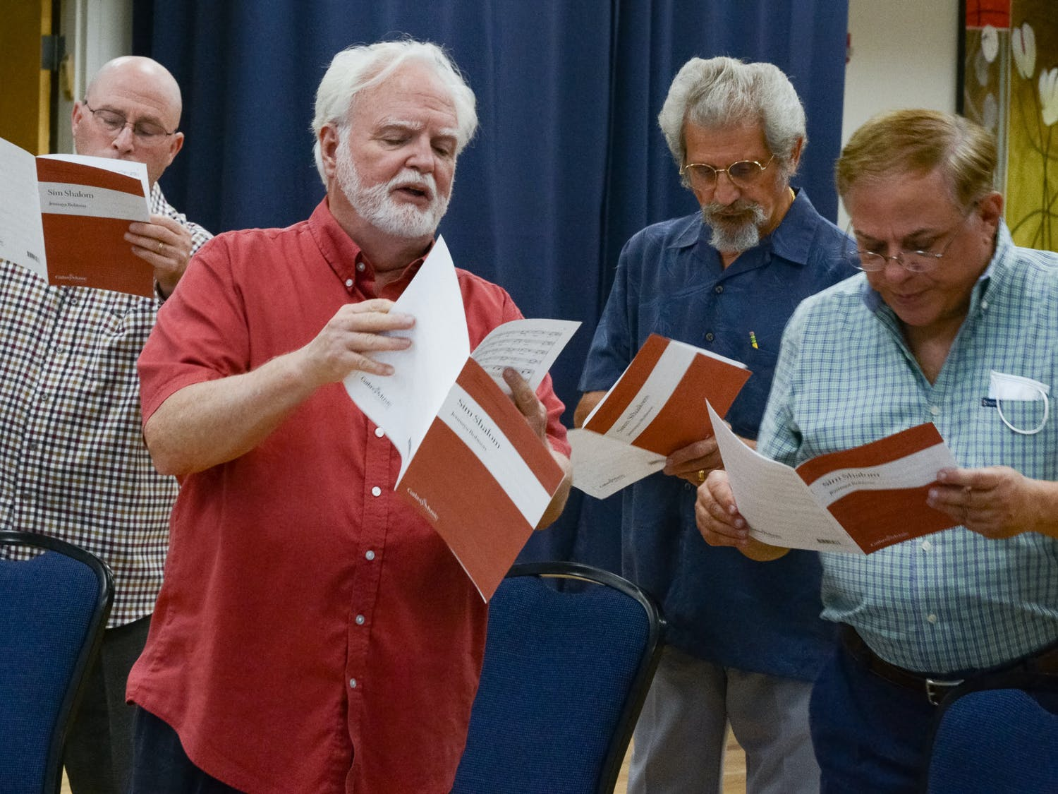 """Willard Kesling (second from left), a UF choral professor and music director and conductor for the ShabbaTones Jewish choir, leads the baritone section of the ShabbaTones in a choir practice on Wednesday, July 28, 2021. """"I will not let art, not let culture die,"""" Kesling said, before the group began their first in-person choir practice since the COVID-19 pandemic halted performances in early 2020."""