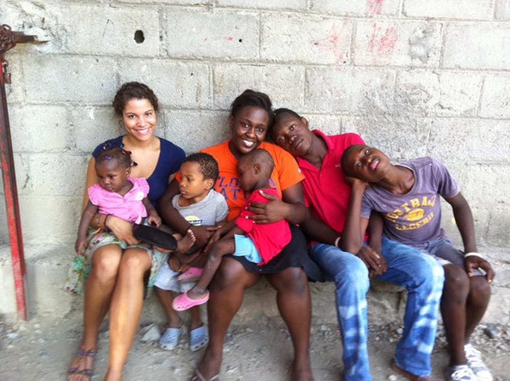 <p>McNair Scholars Jasmine Wright and Bertrhude Albert pose with orphans at the H.O.P.E. Center in Haiti.</p>
