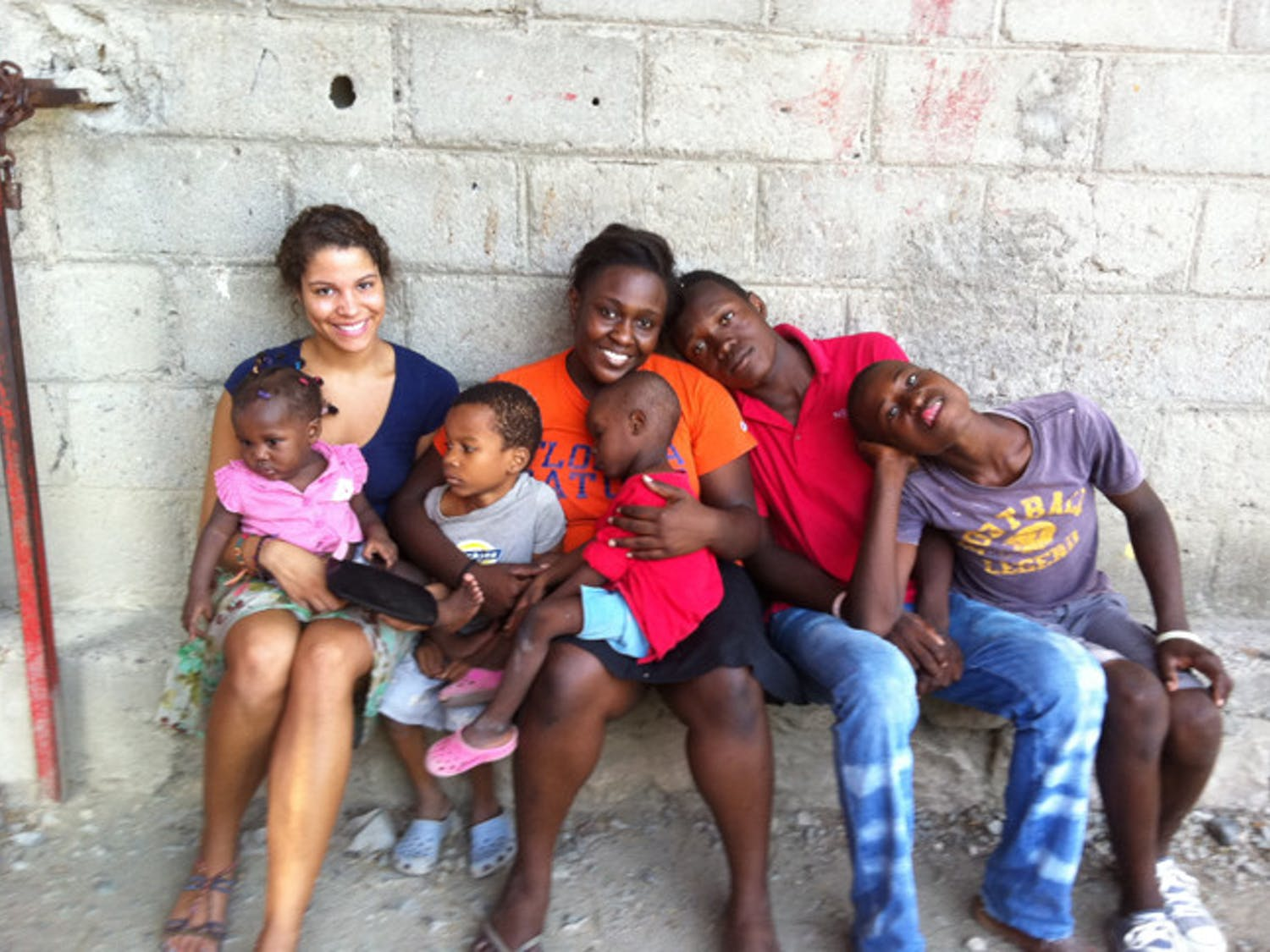 McNair Scholars Jasmine Wright and Bertrhude Albert pose with orphans at the H.O.P.E. Center in Haiti.