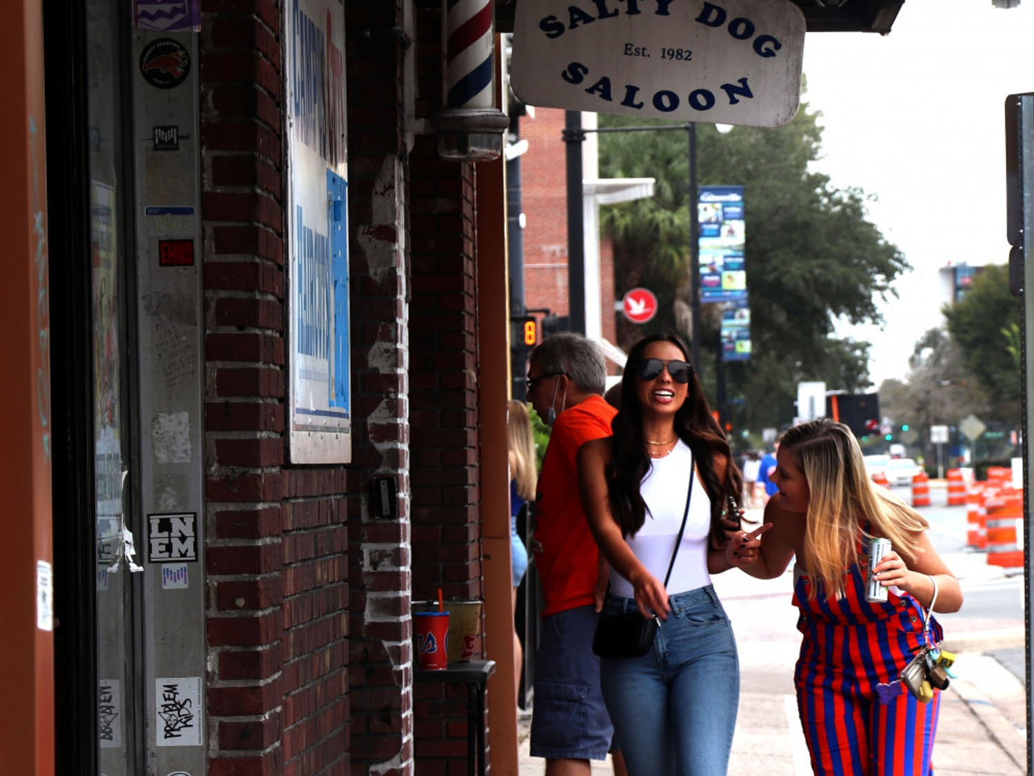 Two women are seen walking past Salty Dog Saloon, located on West University Avenue, on Saturday, Oct. 3, 2020. People are seen partying from morning through midnight for the firs home game. (Chasity Maynard/Alligator Contributor)