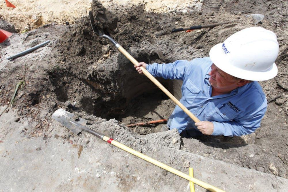 <p>A gas worker for Gainesville Regional Utilities, digs around a broken gas line.</p>