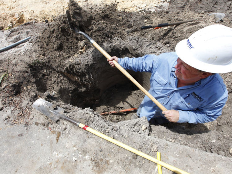 A gas worker for Gainesville Regional Utilities, digs around a broken gas line.