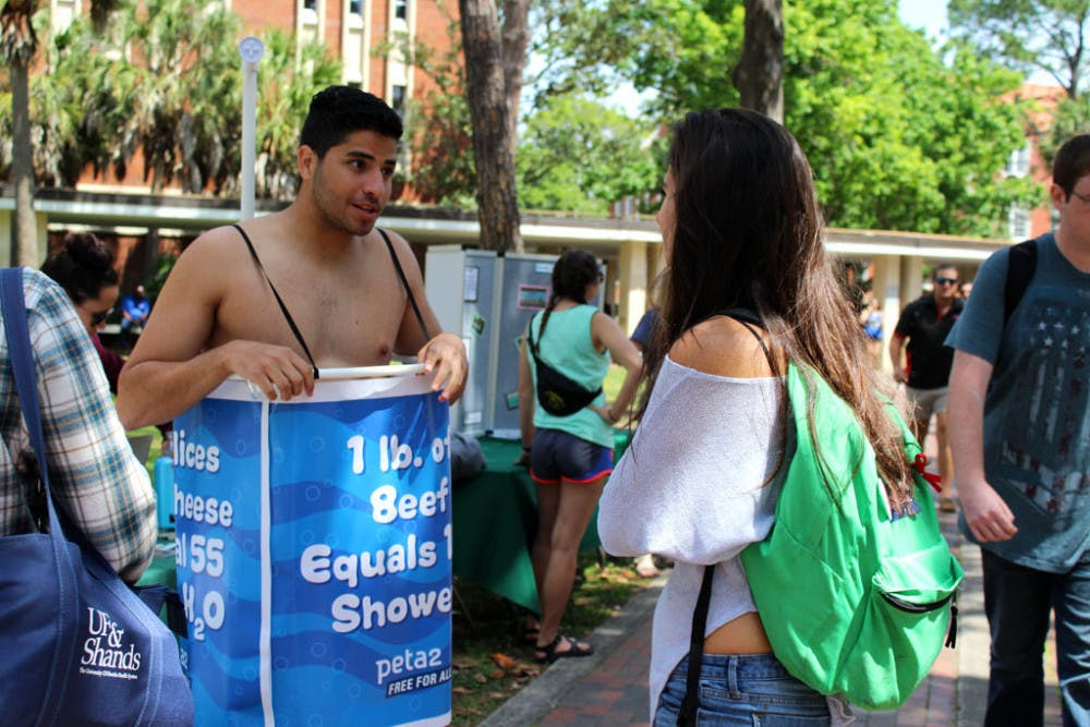 """<p>Manny Rutinel, a 21-year-old UF microbiology and cell science and economics senior, left, promotes the Student Animal Alliance by promoting veganism. Rutinel said it's easy to remember to turn off a faucet while you soap or brush your teeth, but animal agriculture accounts for more environmental problems than any other sector of the environment. """"In order to go green, you have to eat green,"""" he said.</p>"""