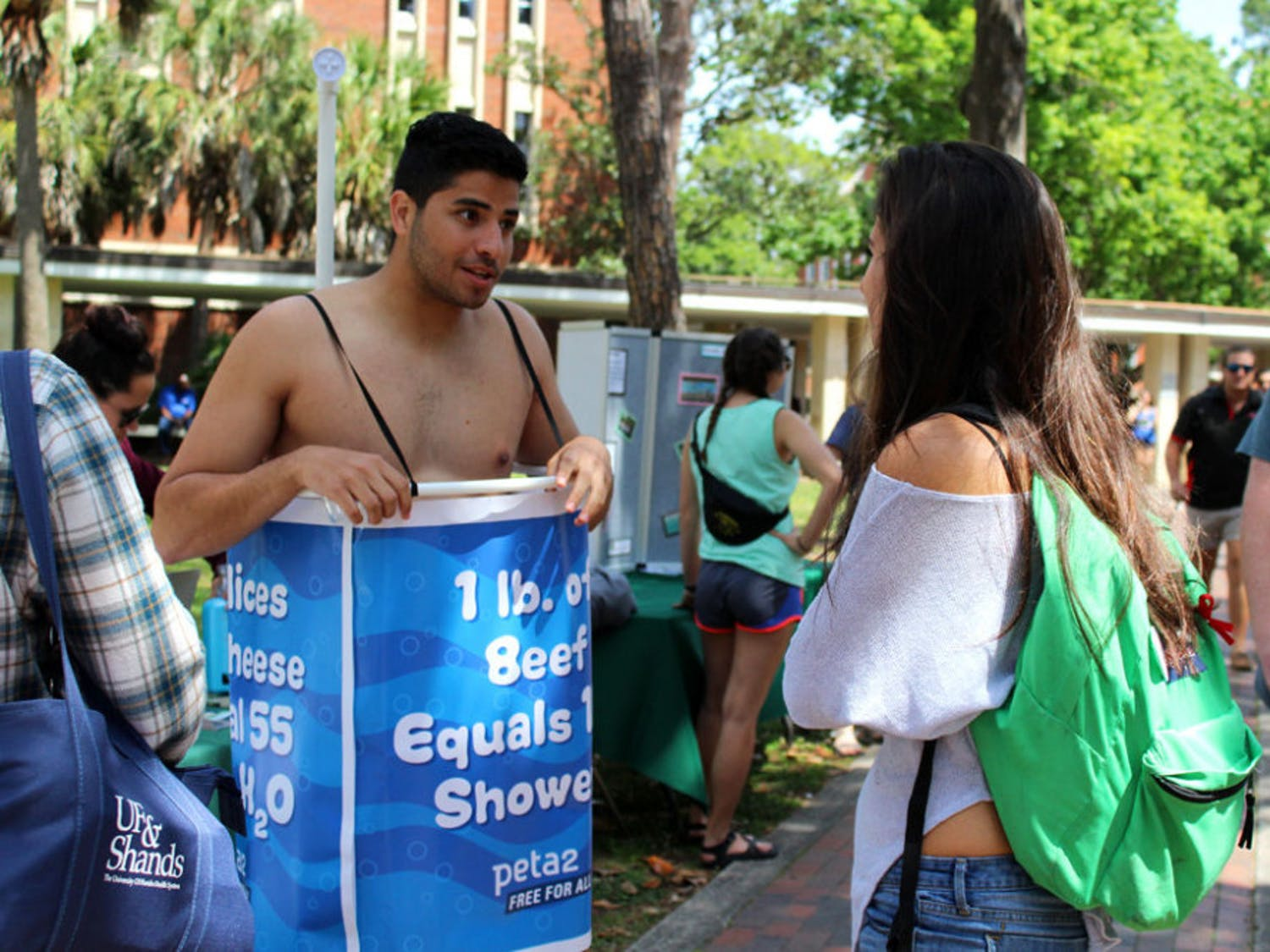 """Manny Rutinel, a 21-year-old UF microbiology and cell science and economics senior, left, promotes the Student Animal Alliance by promoting veganism. Rutinel said it's easy to remember to turn off a faucet while you soap or brush your teeth, but animal agriculture accounts for more environmental problems than any other sector of the environment. """"In order to go green, you have to eat green,"""" he said."""