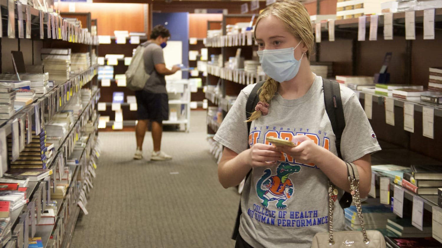 """Madison Bastian, UF health education and behavior fourth-year, shops for her textbooks at the UF Bookstore on Wednesday, Sept. 1, 2021. The top-level Bright Futures' stipend, used by many students to buy textbooks, was taken away this semester. """"I'm very disappointed,"""" Bastian said."""