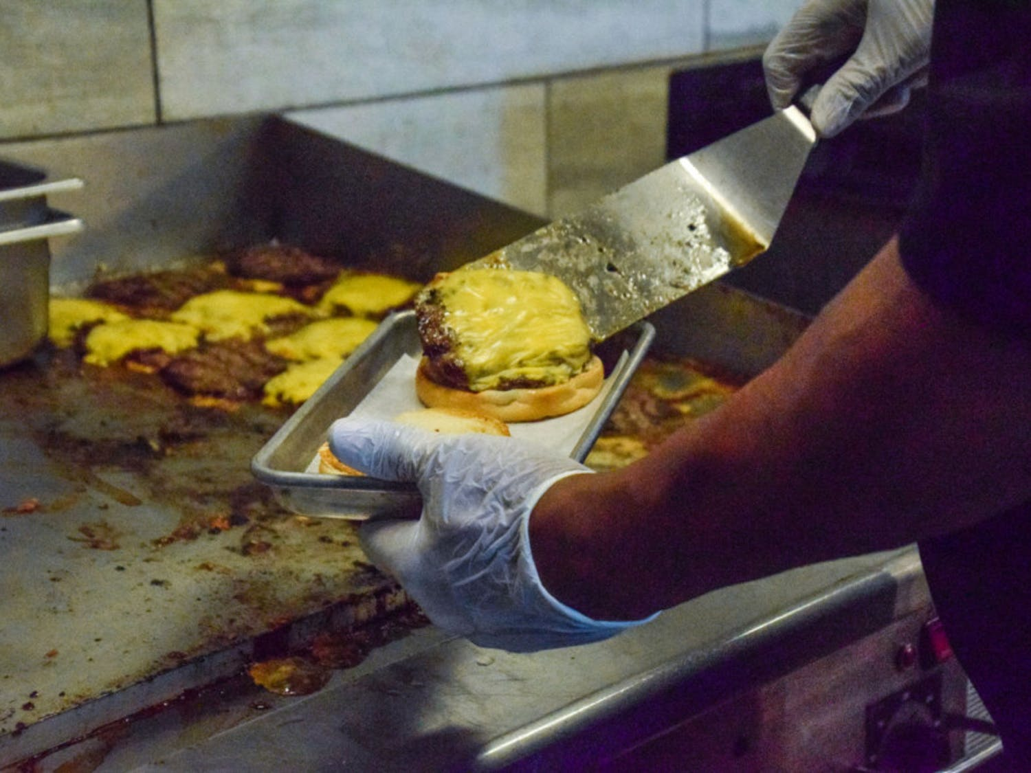 An employee prepares a cheeseburger at The Fresh Food Company. The 2019 Food Service Master Plan by Brailsford & Dunlavey and Petit Consulting said that Aramark's food in the UF dining halls isn't fresh.