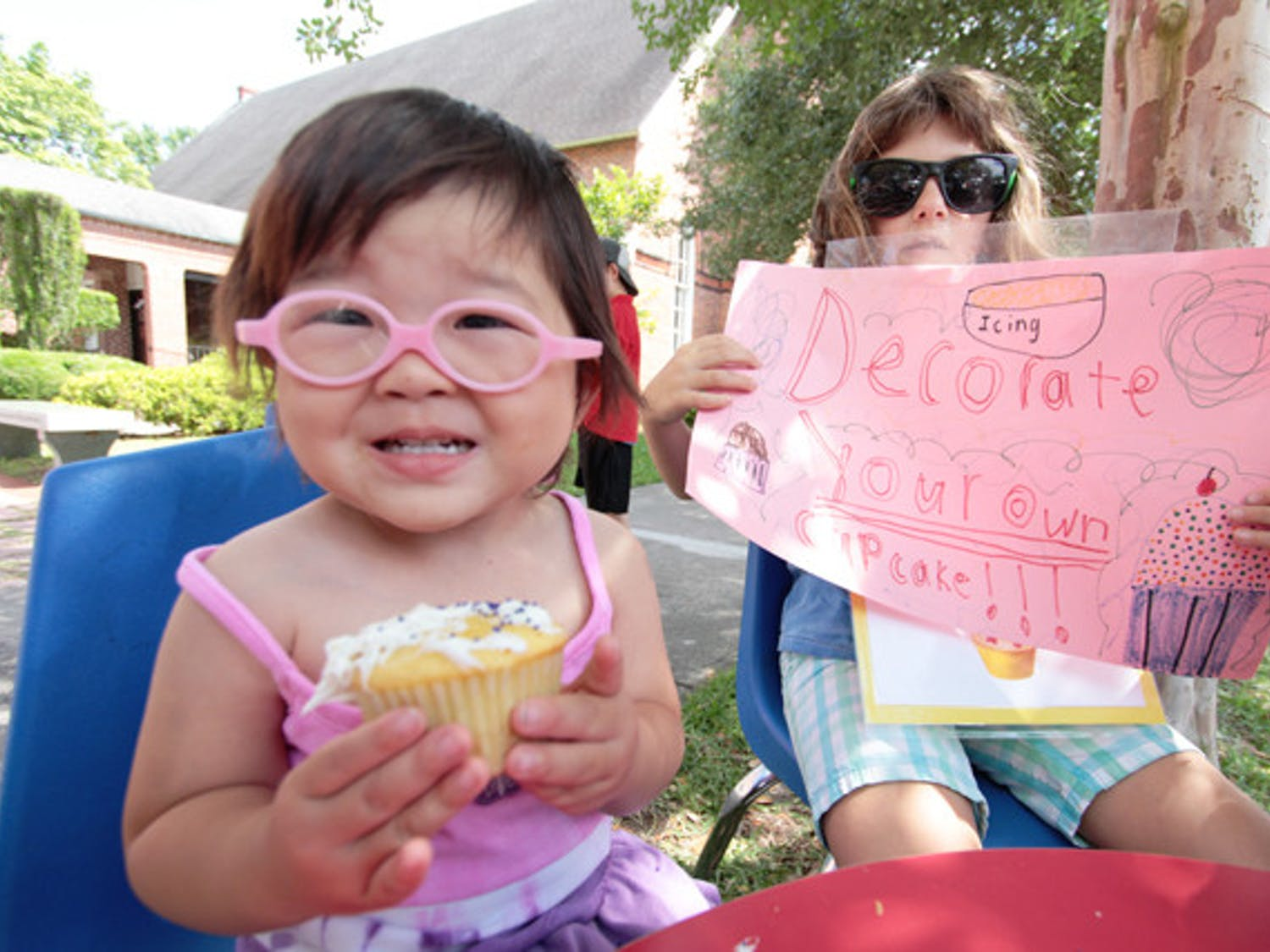 Gainesville resident Mae, 3, shows off a cupcake she iced at the Santa Fe College Spring Arts Festival in 2012 while Jodie, 8, holds a sign promoting the cupcake-decorating to raise money for FUMPers, the preschool of First United Methodist Church.