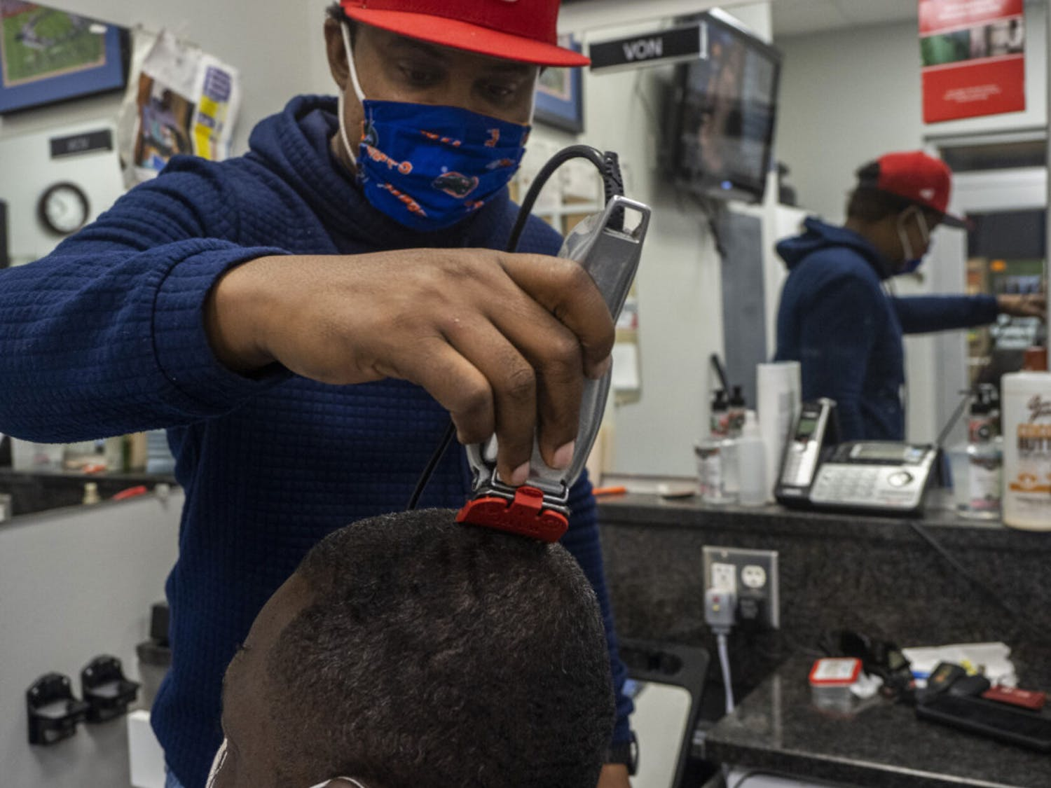 Von Brockington, a barber at The Reitz Union Barber Shop, is seen trimming John Smith's hair on Monday, Oct. 19, 2020.