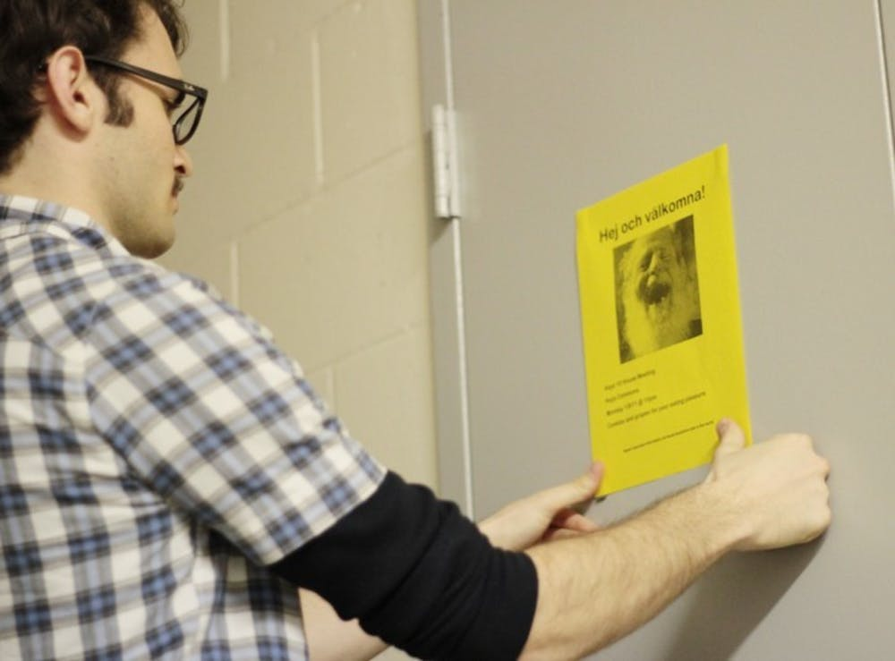 <p>Second-year resident assistant Tyler McCann hangs fliers around his dorm area to alert residents of his spring semester housing meeting.</p>
