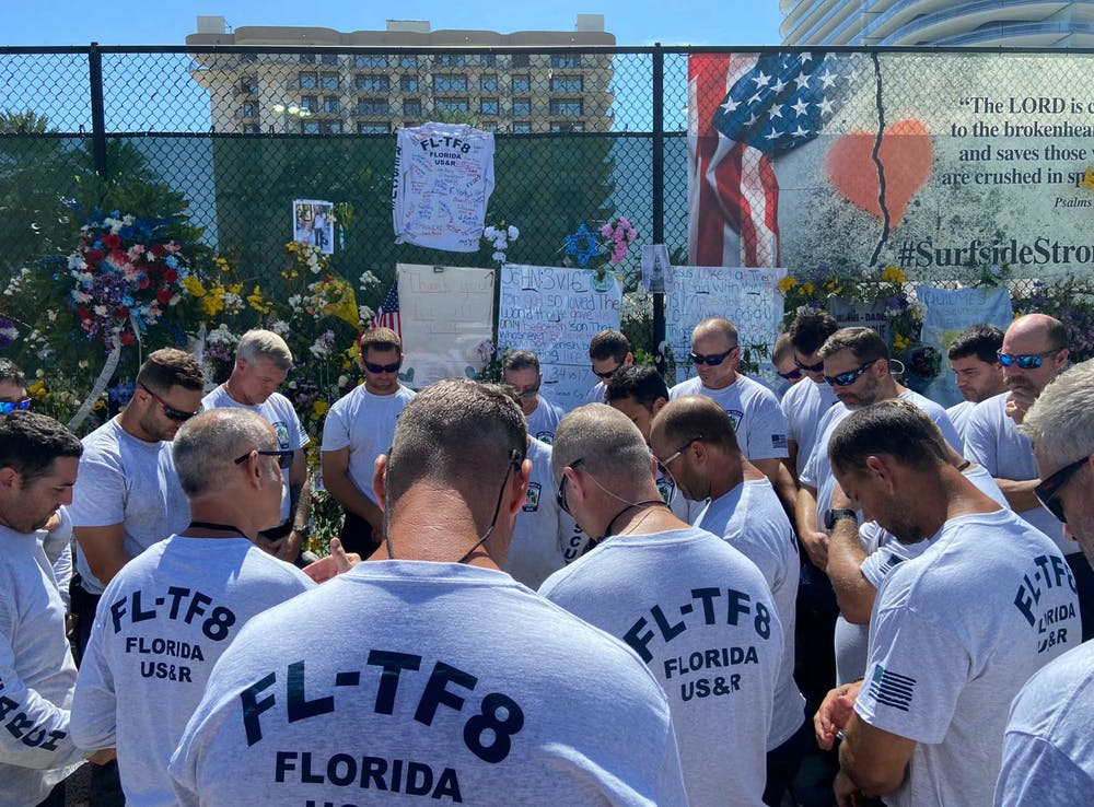 Florida Task Force 8 members bow their heads in front of a memorial wall in Surfside, Florida. Gainesville Fire Rescue sent eight members to Surfside to aid in rescue efforts after the partial collapse of the Champlain Towers South condominium on June 24.