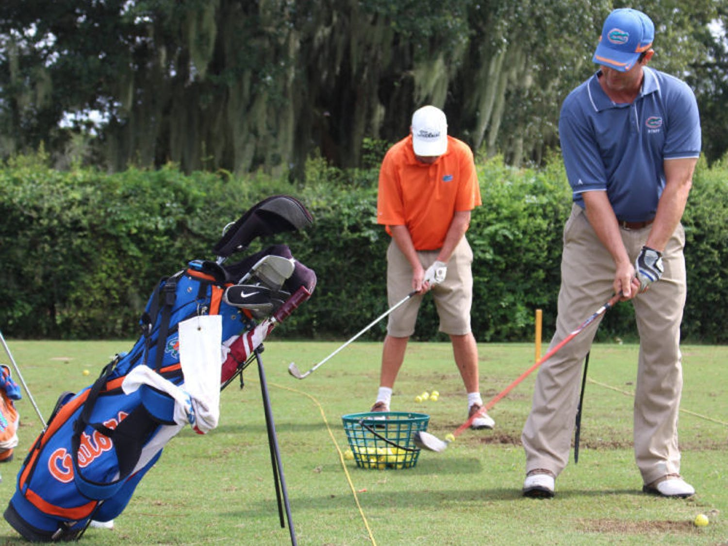 Maintenance staff members Scott Dowling, back, and Mike Brown, front, line up to hit at the driving range of UF's Mark Bostick Golf Course on Wednesday.
