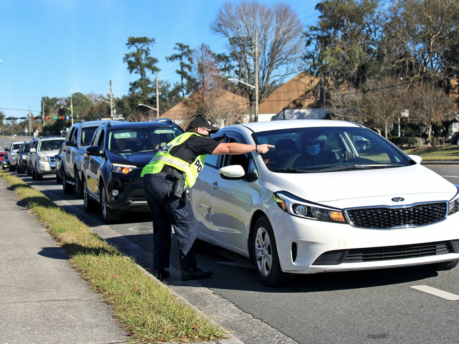 J. Evans, a Gainesville Police Department officer, directs traffic into Malcom Randall VA Medical Center on Monday, Jan. 18, 2021. A long line of traffic formed outside the hospital as Alachua County residents 65-years-old and older waited to receive COVID-19 vaccines.