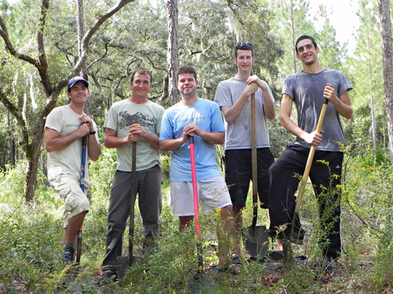 Jacob Cravey, 30; Ivor Kincaide, 38; Christopher Wolf, 25; Alex Potts, 25; and David Hanan, 24, planted aroundtrees Friday morning at Paynes Prairie as part of a project with Neutral Gator.