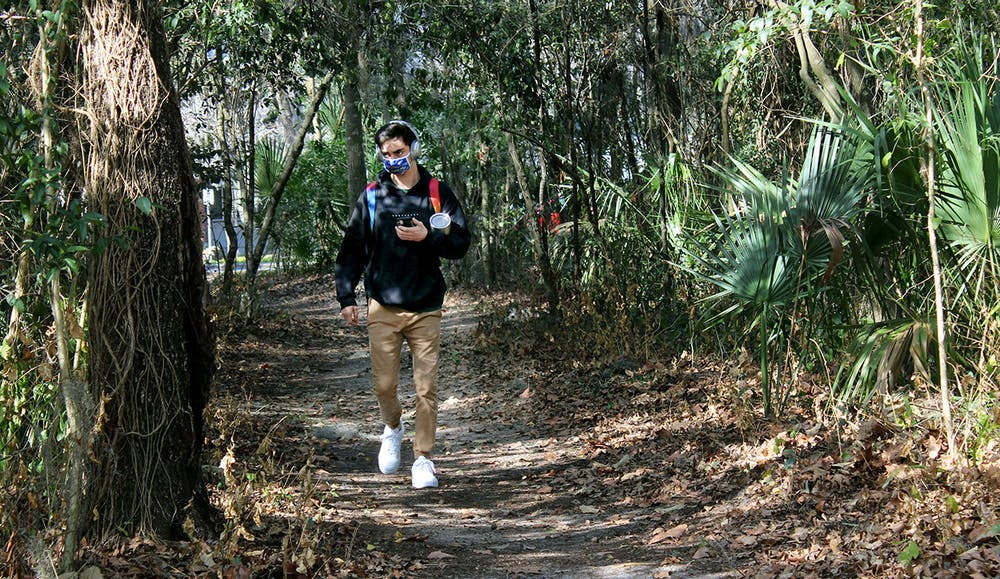 """Matt Raulerson, 20, a forest resources and conservation junior, walks on a path through the McCarty Woods Conservation Area on Thursday, Feb. 4, 2021. Raulerson expressed disappointment at the news that the conservation area has been approved as a possible future site for construction. """"It's horrible,"""" he said. """"It would take away all the beauty of it. It's something I pass everyday I walk to class and it's something I love looking at."""""""
