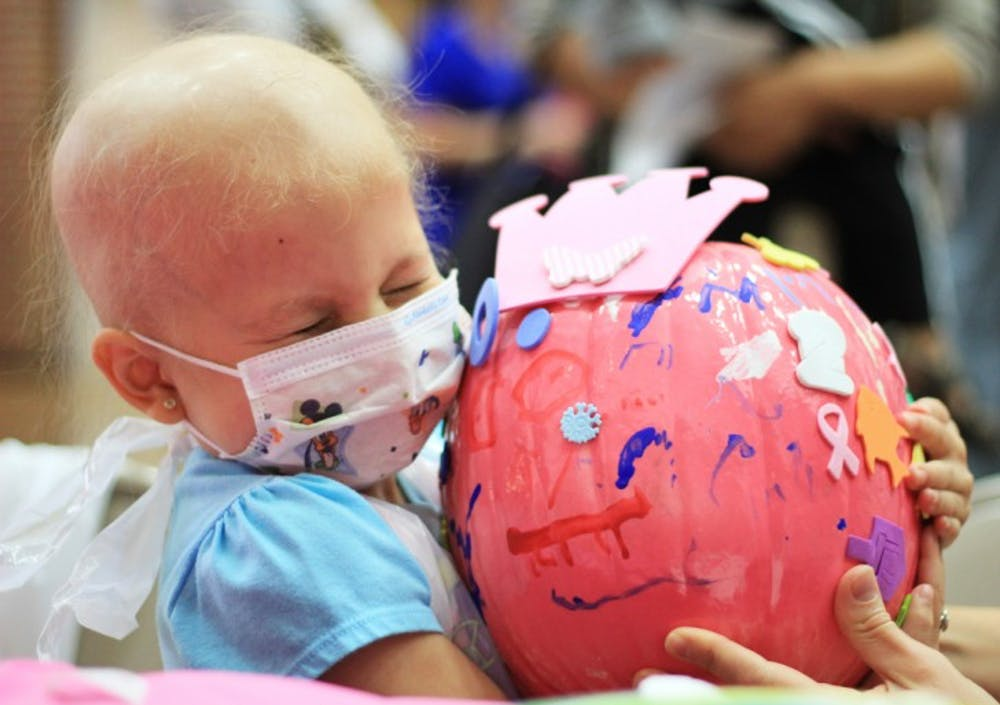 <p>Madison, a 4-year-old undergoing treatment for leukemia at Shands Hospital for Children at UF, holds her pink pumpkin on Wednesday morning as part of an event for patients and families.</p>