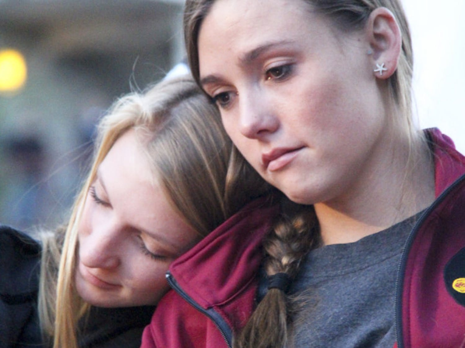 19-year-old FSU statistics freshman Olivia Heartsell, (left), leans on her teammate Amber Milner, a 22-year-old psychology junior, during the Gathering of Unity at the university's Integration Statue on Thursday evening.