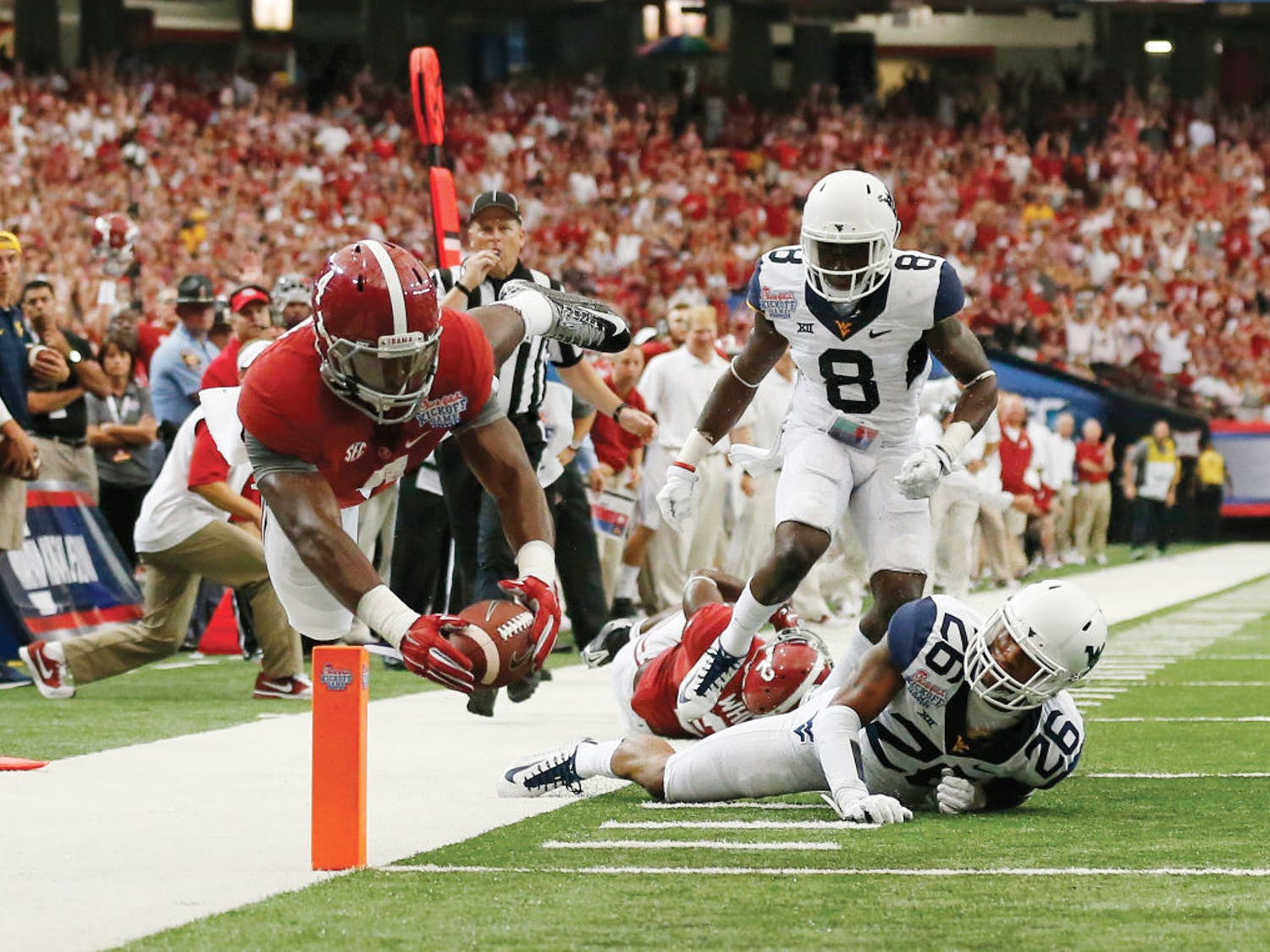 Alabama running back T.J. Yeldon (4) dives into the end zone for a touchdown as West Virginia's Travis Bell (26) and Karl Joseph (8) defend in the first half of an NCAA college football game Saturday, Aug. 30, 2014, in Atlanta.