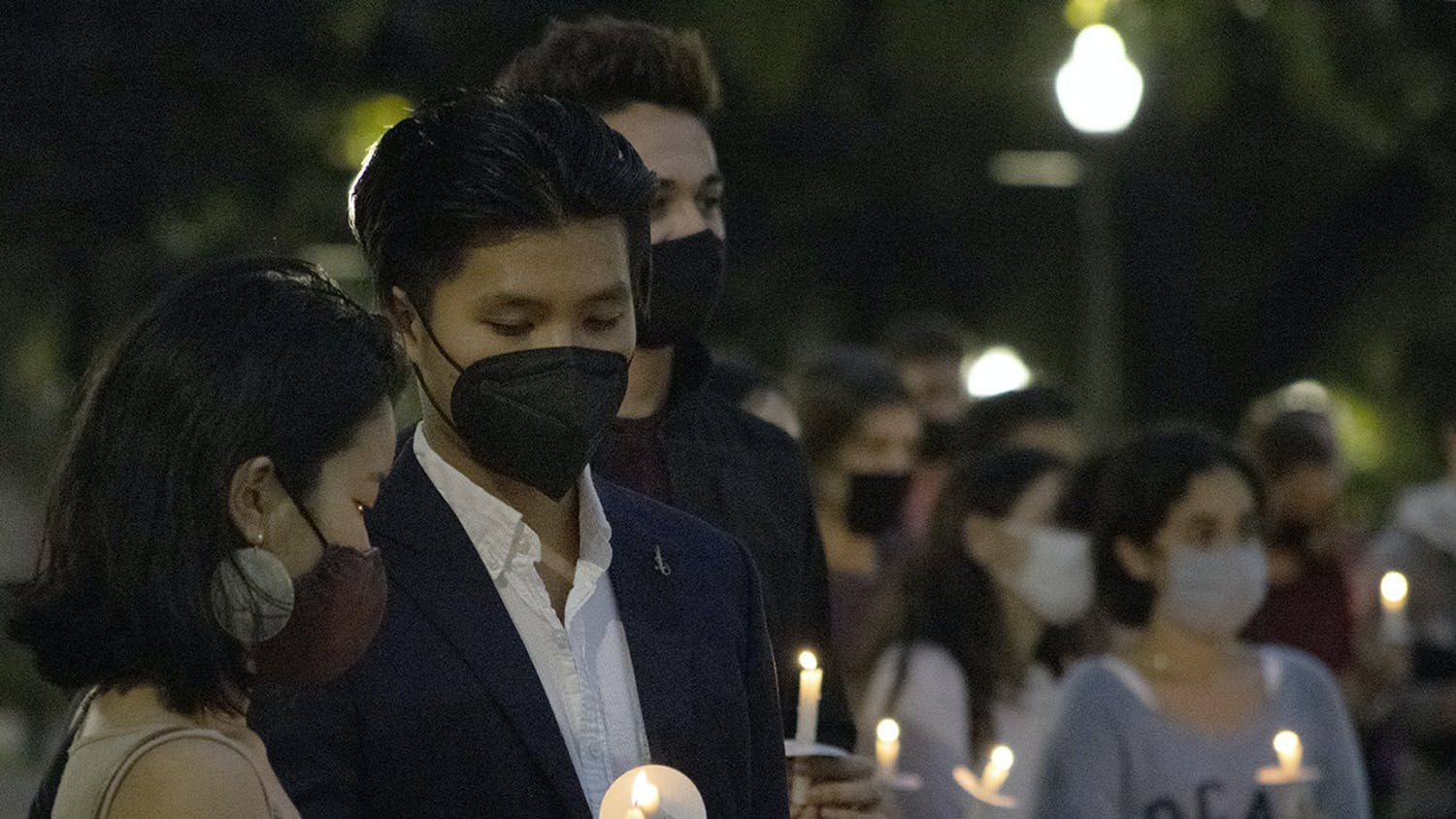 Two people light each other's candles during an event on Sunday, Feb. 14, 2021 to honor those killed during a school shooting in Parkland, Florida three years ago.