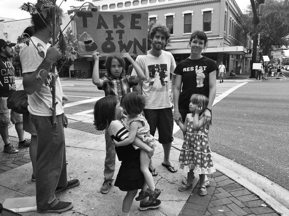 """<p><span id=""""docs-internal-guid-8093e4f2-3dbc-d948-24e2-2611b56278bd""""><span>Protesters young and old stand at the corner of Southeast University Avenue and Main Street in opposition to the """"Old Joe"""" Confederate soldier statue. Demonstrators shouted through megaphones across all four corners of the intersection chants such as """"Old Joe has got to go"""" and """"No hate. No KKK. No fascist USA.""""</span></span></p>"""
