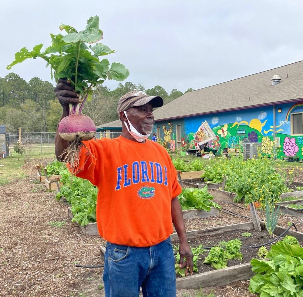 <p>Joseph Scott, 60, stands next to his personal garden at GRACE Marketplace. [Photo courtesy to the Alligator]</p>