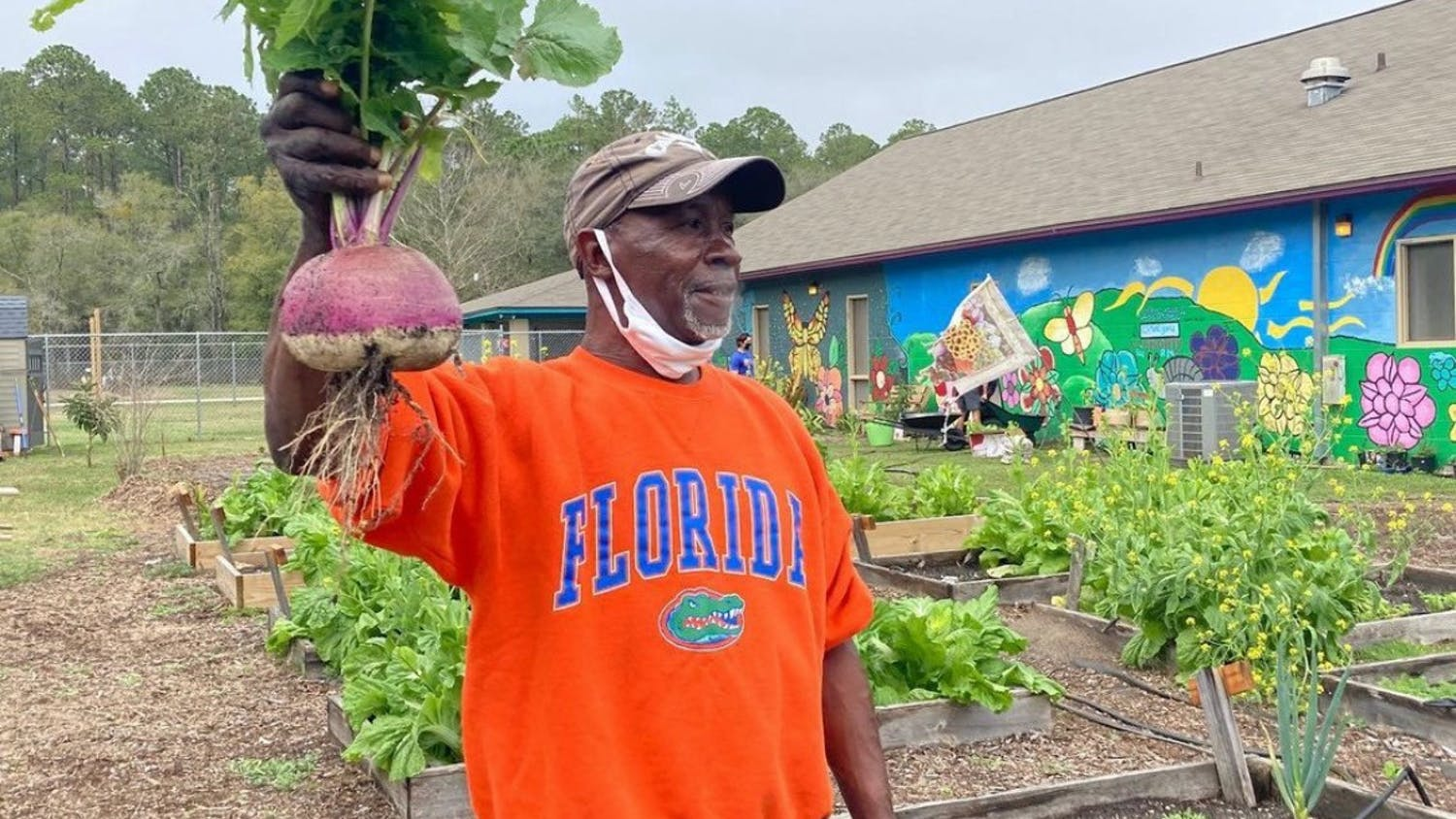 Joseph Scott, 60, stands next to his personal garden at GRACE Marketplace. [Photo courtesy to the Alligator]