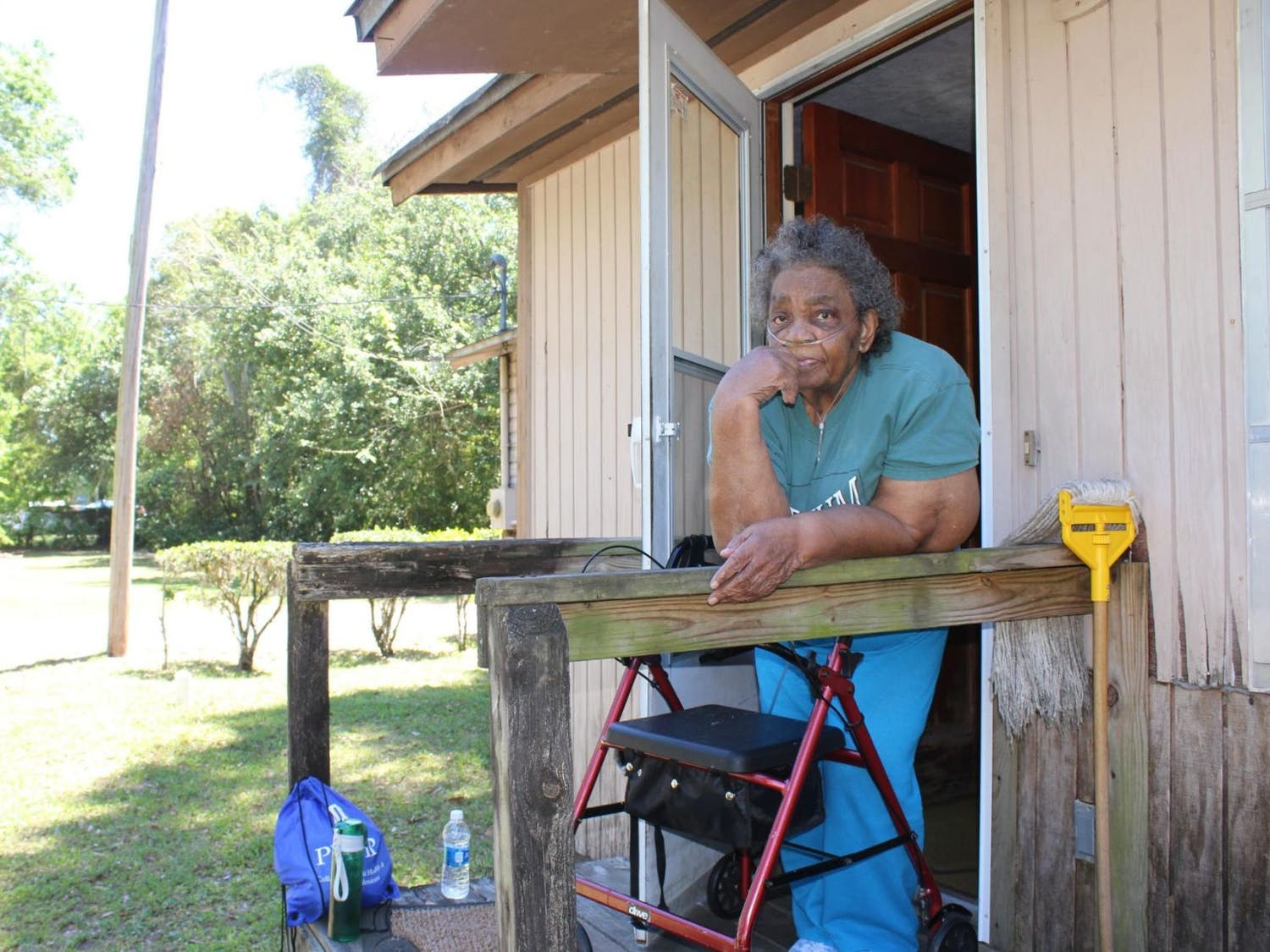 Mamie Leath, 89, watches as UF students help clear fallen leaves from her home in Gainesville's Porters Community on Saturday as a part of UF Student Government's inaugural The Big Event. Leath said she felt grateful the students volunteered their time clearing her yard of leaves and miscellaneous junk, like rusted bicycles and an armchair.
