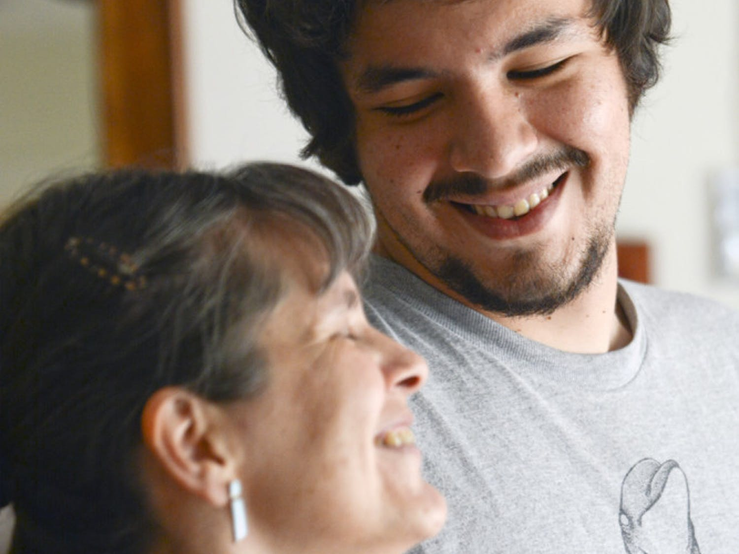 Claudia Castagliola, 45, laughs with her eldest son, Cristobal Gonzalez, 23, in her home's living room. The two will graduate from a PhD program and a Master's program, respectively, this week.