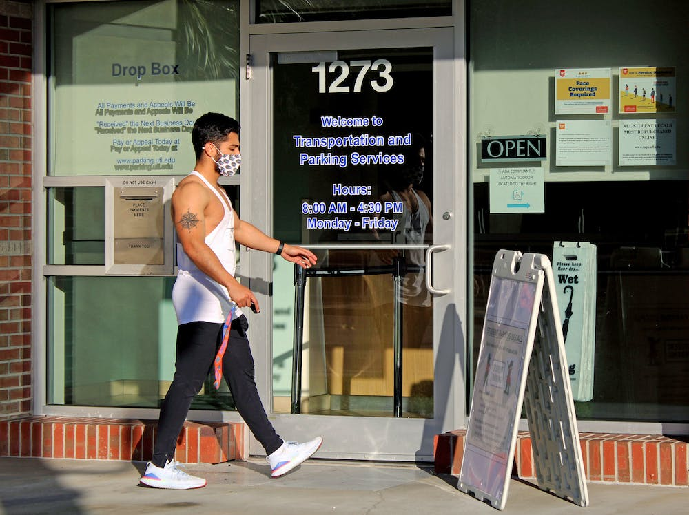 Julian Cruz, 20, applied physiology and kinesiology junior walks into the UF Transportation and Parking Services office on Thursday, Jan. 14, 2021. He was applying for a parking decal for the UF Health Shands Hospital parking lot.