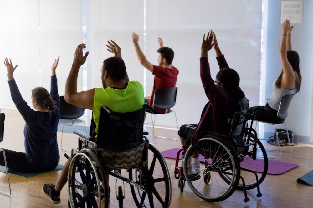 """<div dir=""""auto"""">UF students participating in yoga class put on by UF's Disability and Resource Center.</div>"""