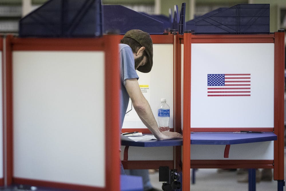 <p>A voter reads his ballot at the Hamilton County Board of Elections as early voting begins statewide, Wednesday, Oct. 12, 2016, in Cincinnati.</p>